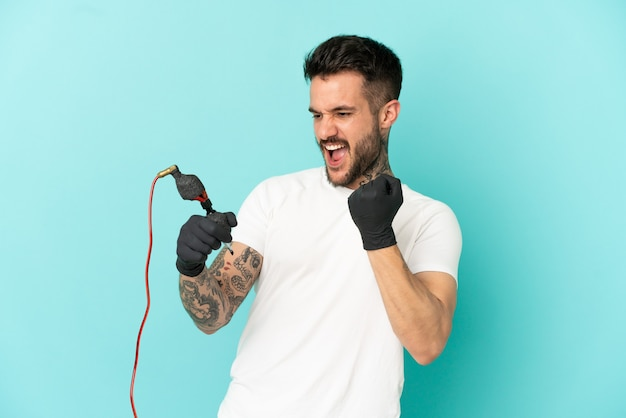 Tattoo artist man over isolated blue background celebrating a victory