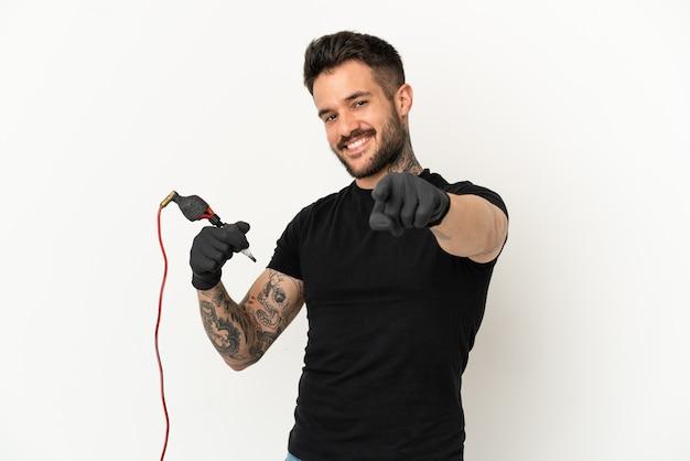Человек-татуировщик на изолированном белом фоне, указывая спереди счастливым выражением лица