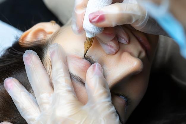 문신 아티스트는 속눈썹의 영구 화장을 수행합니다.