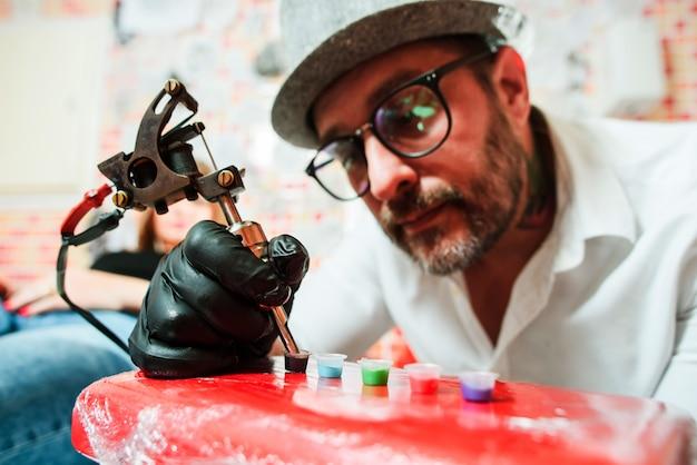 Тату художник готовит инструменты для татуировки