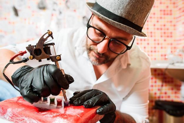 Tattoo artist prepares tools for tattooing