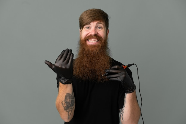 Tattoo artist redhead man isolated on blue background inviting to come with hand. happy that you came