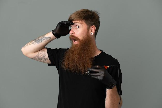 Рыжий татуировщик на синем фоне делает неожиданный жест, глядя в сторону