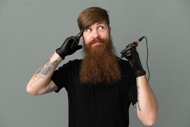 疑問と思考を持っている青い背景に分離されたタトゥーアーティスト赤毛の男