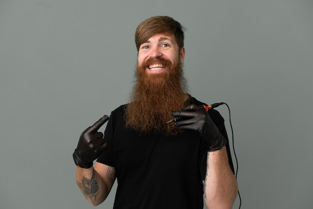 제품을 제시하기 위해 측면을 가리키는 파란색 배경에 고립 된 문신 예술가 빨간 머리 남자