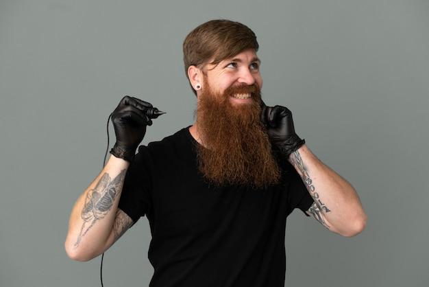 見上げながらアイデアを考えている青い背景に分離されたタトゥーアーティスト赤毛の男