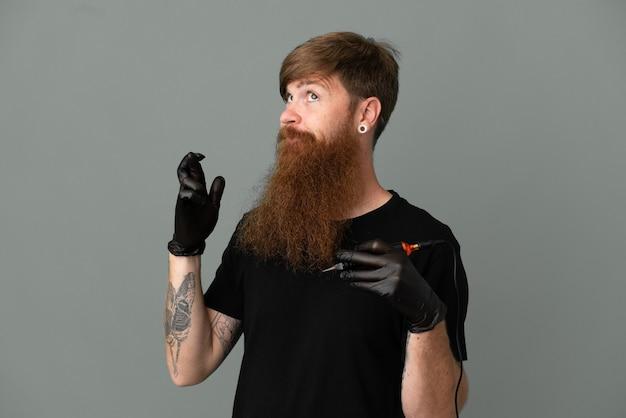 指が交差し、最高を願って青い背景に分離されたタトゥーアーティスト赤毛の男