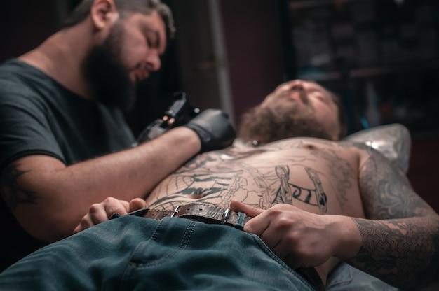 タトゥーを作るプロセスを示すタトゥーアーティスト Premium写真