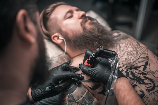 タトゥーを作るプロセスを示すタトゥーアーティスト