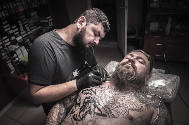 Художник-татуировщик работает над профессиональным тату-автоматом в студии.
