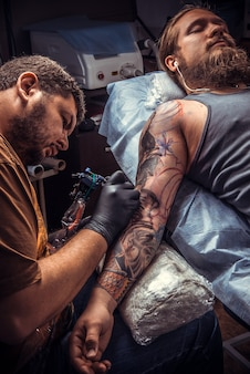 문신 예술가는 스튜디오에서 일합니다 ./ 전문 문신가는 문신 가게에서 문신 그림을 만듭니다.