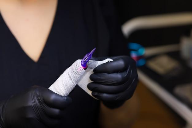 문신 아티스트는 영구 화장 절차를 위해 문신 기계를 준비합니다.