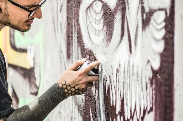 Татуировка граффити-писателя с росписью окрасила его темную картину на стену. современный художник за работой