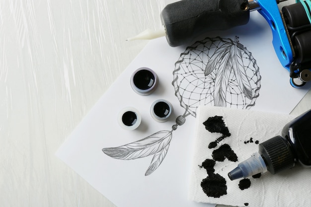 Тату-машина, эскиз и принадлежности на столе