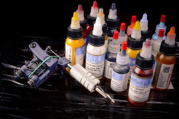 Машина татуировки с множеством бутылок цветных чернил, изолированных на черном.