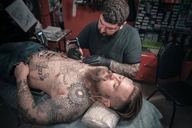 Мастер-татуировщик демонстрирует процесс изготовления тату в мастерской студии.