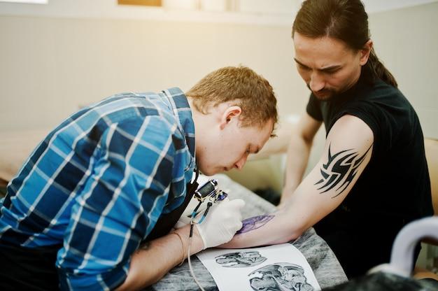 Tattoo master make tattoo for rocker man