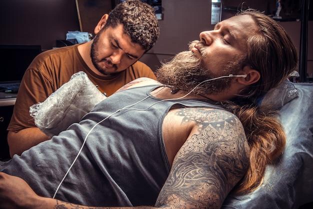 Мастер татуировки показывает процесс в тату студии