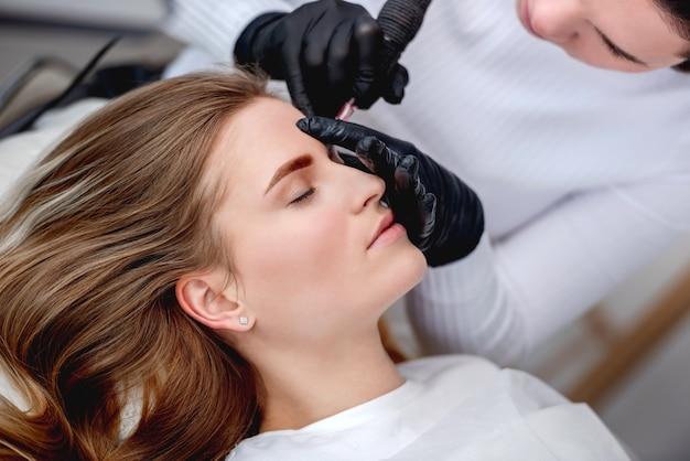 Тату мастер перманентного макияжа делает микроблейдинг красивых бровей для привлекательной блондинки