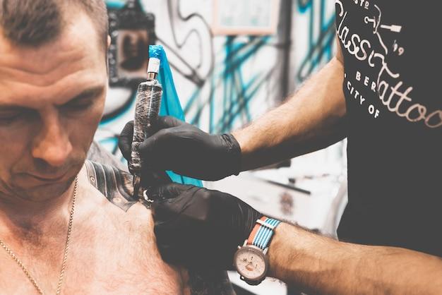 Тату салон. тату мастер татуирует мужчину на плече. машина татуировки, безопасность и гигиена на работе. крупный план, тонировка, татуировщик