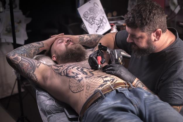 Тату-специалист делает татуировку на коже в тату-салоне