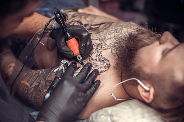 Тату-специалист, работающий с профессиональным тату-пистолетом