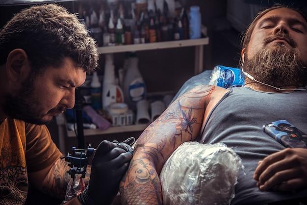 문신 전문가는 문신 가게에서 일합니다. / 문신 스튜디오에서 문신을하는 장갑을 끼고있는 남자.