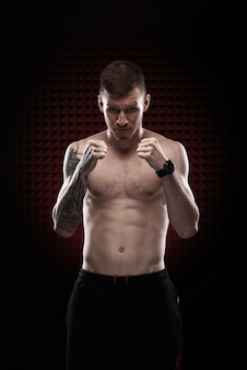 Tattoo strong boxer stand in front of dark background