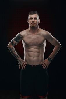 Тату сильный боксер стоять перед темным фоном