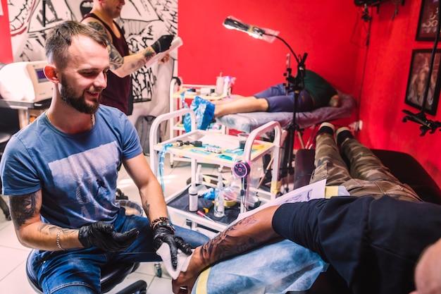 Студия татуировки с мастерами и клиентами