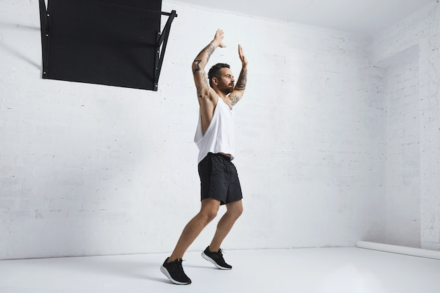 Татуированный и мускулистый спортсмен, выполняющий прыжки, изолирован на белой кирпичной стене рядом с черной перекладиной, глядя вправо