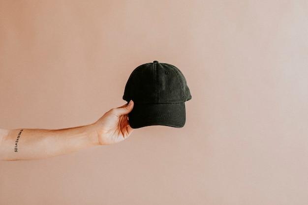 Tattooed arm holding a black cap