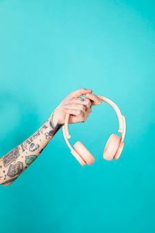 Tattooed arm holding a pink headphones