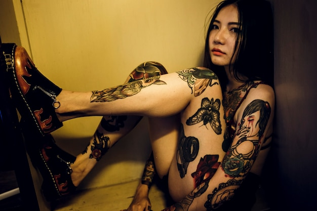 Tattooed asian woman sitting in a box