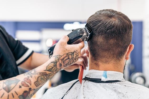 이발소에서 전기 기계를 사용하여 백인 남자의 머리를 자르는 문신을 한 이발사