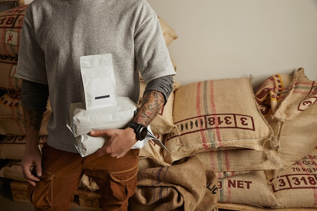 Tattooed barista holds blank package bags with freshly baked coffee beans ready for sale and delivery