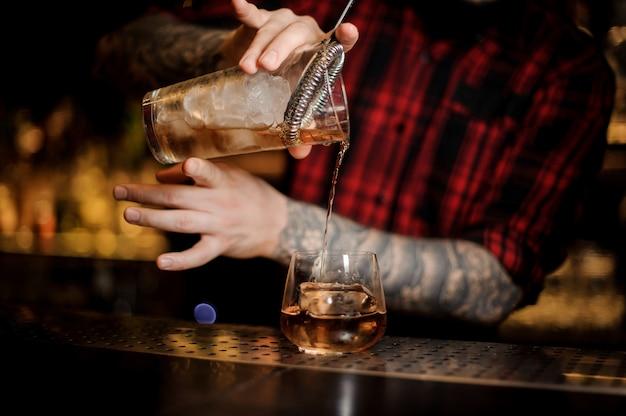 Татуированный бармен наливает свежий напиток в бокал для виски