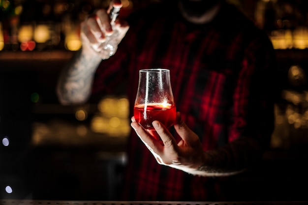 Tattooed barman sprinkling bitter into the glass with fresh red sweet cocktail on the bar counter