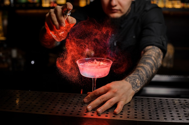 Tattooed bartender spraying on the delicious cocktail from the special vaporizer on the bar counter