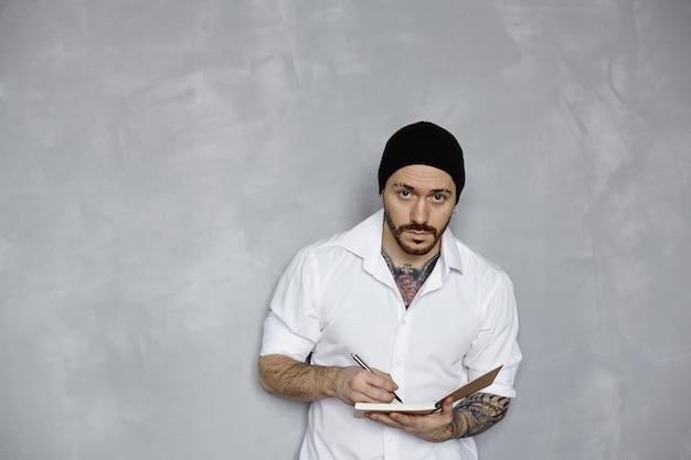 흰 셔츠와 검은 모자에 문신을 한 수염 난 남자는 메모장에 메모를 작성합니다.