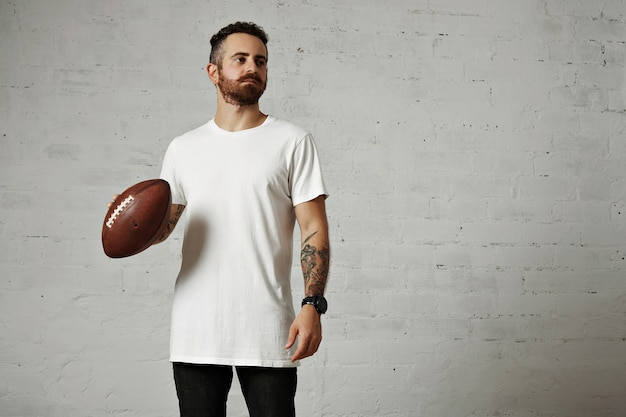 Tattooed and bearded model in plain white shortsleeve t-shirt holding a leather football on gray wall