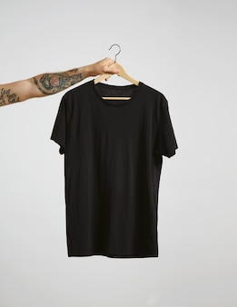 Татуированная рука байкера держит вешалку с пустой черной футболкой из тонкого хлопка премиум-класса, изолированной на белом