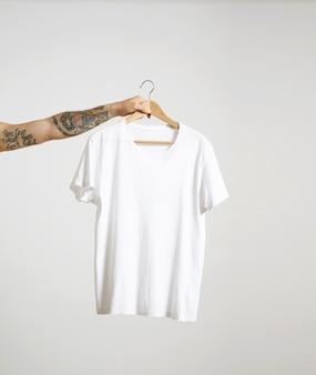 Татуированная рука байкера держит вешалку с пустой белой футболкой из тонкого хлопка премиум-класса, изолированной на белом