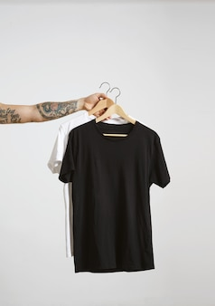 Tattooed biker hand holds wooden hangs with blank black and white t-shirts from premium thin cotton, isolated on white