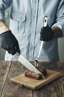 Tattooed butcher hands in black gloves keep knife cut slice of grilled meat on wooden board
