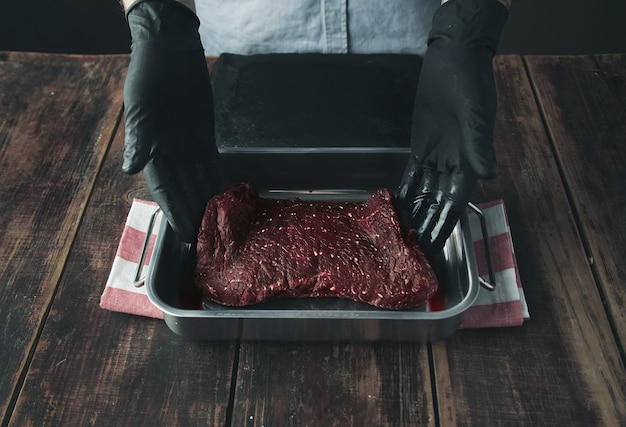 Tattooed butcher hands in black gloves offer piece of fresh raw meat in stainer with juice or blood on camera