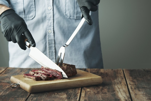 Tattooed butcher hands in black gloves with knife slice piece of grilled meat on wooden board