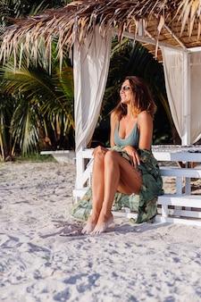 Donna caucasica tatuata in pantaloncini di jeans e top corto alla moda verde in spiaggia