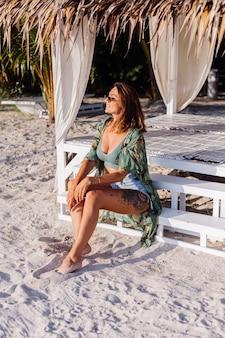Татуированная кавказская женщина в джинсовых шортах и модном зеленом топе на пляже