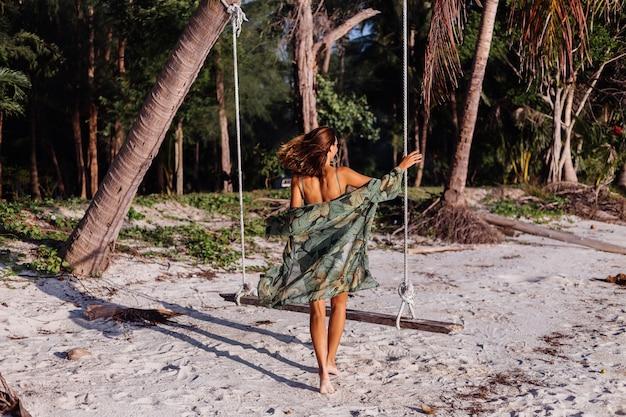 ビーチでデニムのショートパンツと緑のトレンディなクロップトップで入れ墨の白人女性